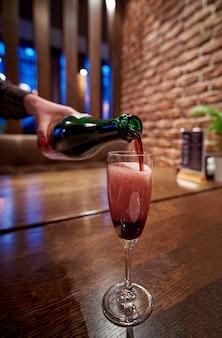 Roter funkelnder champagner mit luftblasen im glas. der kellner schüttet den champagner ins glas.