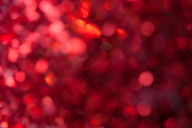 Roter funkelnder hintergrund von den kleinen pailletten, nahaufnahme
