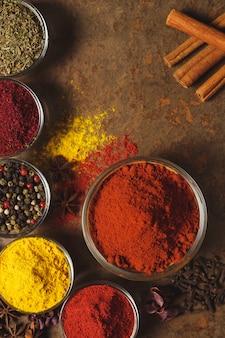 Roter gemahlener paprika. platz für text. verschiedene arten von gewürzen in einer schüssel auf einer steinmauer. der blick von oben