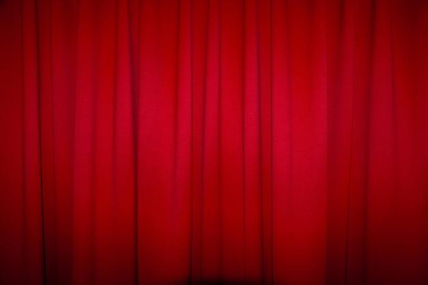 Roter geschlossener vorhang mit einem hellen stellengebrauch für hintergrund