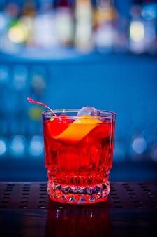 Roter getränkecocktail im glas mit kirsch- und orangenschale auf holztisch in der bar