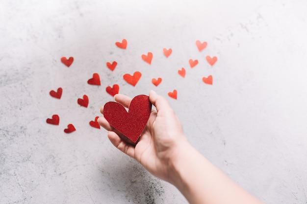 Roter glitzernder herzförmiger karton auf der hand und kleine herzen auf weißem hintergrund. konzept der liebe und valentinstag.