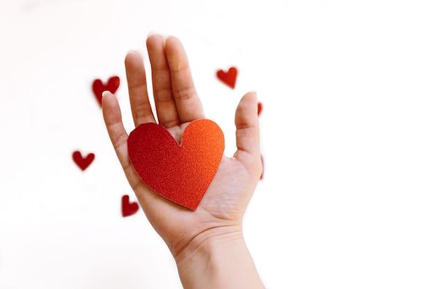 Roter glitzernder herzförmiger karton auf der hand und kleine herzen auf weißer oberfläche. konzept der liebe und valentinstag.