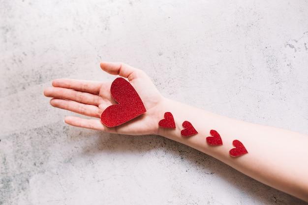 Roter glitzernder herzförmiger karton auf der hand und kleine herzen auf weißer oberfläche. liebe und valentinstag konzept.
