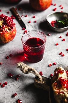 Roter granatapfelsaft in einem glas, reifen und geschnittenen granatapfel und einem zweig minze auf einem grauen betonhintergrund. konzept für vitamine, antioxidantien und naturkost. flache lage. draufsicht.