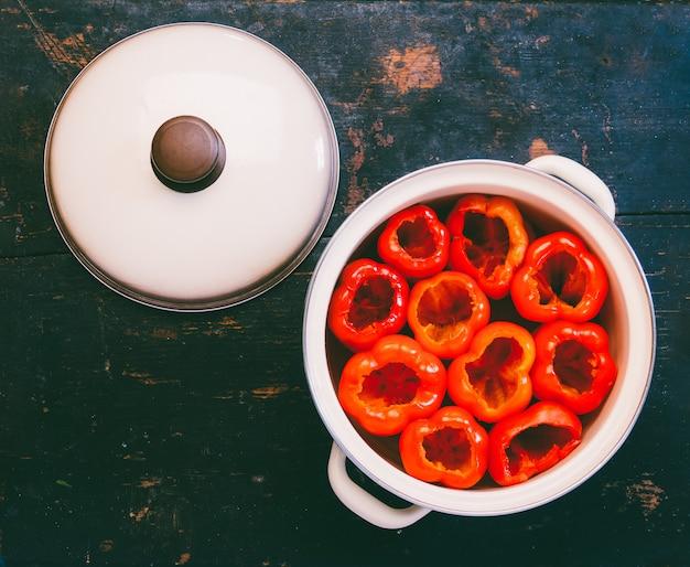 Roter grüner pfeffer, der von den samen abgezogen wurde, bereitete sich für das anfüllen in einer kasserolle, großaufnahme von oben vor
