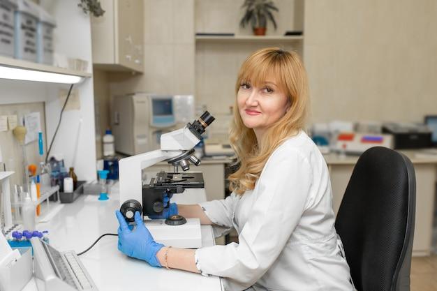 Roter haarfrauenlabortechniker, der durch mikroskop schaut, analysiert blut.