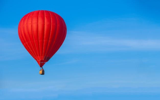 Roter heißer luftballon im blauen himmel. reisehintergrund