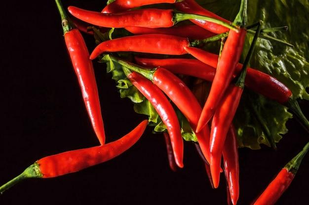 Roter heißer pfeffer auf schwarzem hintergrund auf salatblatt
