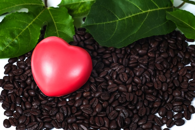Roter herzball auf frischen kaffeebohnen auf weißem hintergrund.