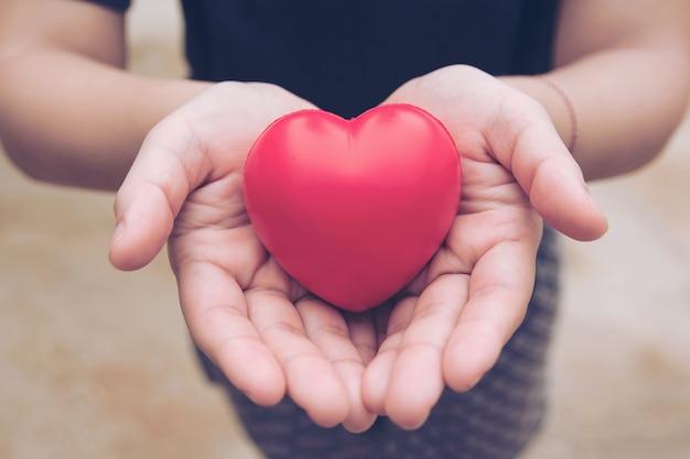 Roter herzball: stressabbau-schaumball die rote herzform auf frauenhand. geschenk valentinstag