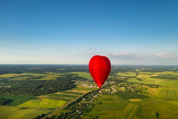 Roter herzförmiger ballon mit menschen über grünen feldern und wäldern.