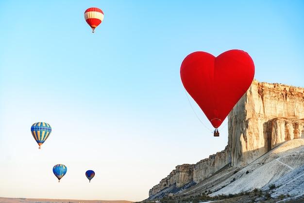 Roter herzförmiger luftballon, der im himmel fliegt