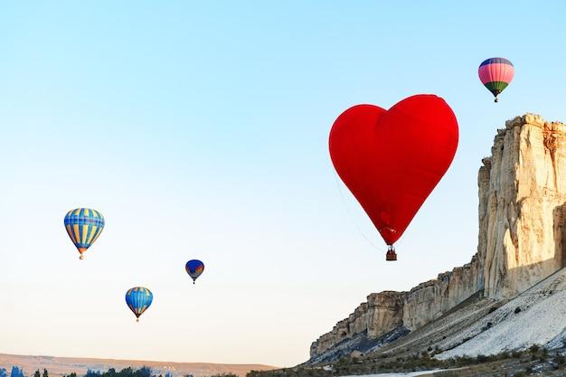 Roter herzförmiger luftballon, der im klaren himmel fliegt