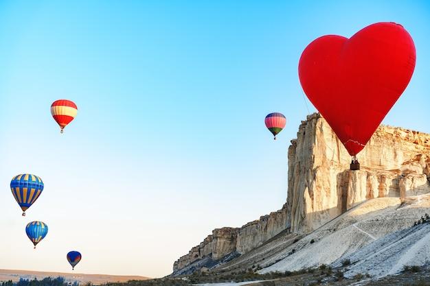 Roter herzförmiger luftballon, der in den himmel fliegt