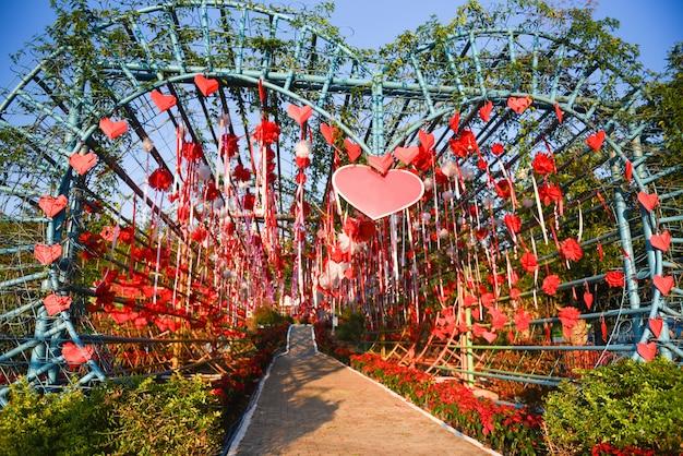 Roter herzpapierschnitt und -band, die am liebestunnelherzen hängt, formten draußen im ereignisvalentinstag oder -hochzeitstag mit blumengehweg