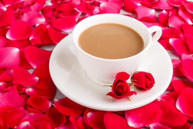 Roter hintergrund der rosafarbenen blumenblätter und ein tasse kaffee.