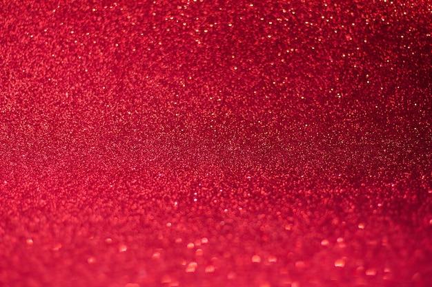 Roter hintergrund mit bokeh und glitzer, valentinstag, weicher fokus des weihnachts- und neujahrshintergrunds