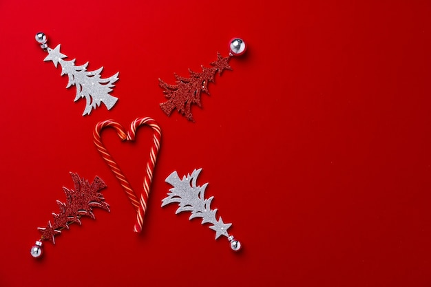 Roter hintergrund mit geschnitzter hölzerner weihnachtsbaum-draufsicht