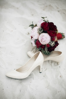 Roter hochzeitsblumenstrauß liegt auf weißen schuhen der braut