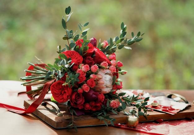 Roter hochzeitsstrauß mit hochzeitsdekor auf einem tisch.
