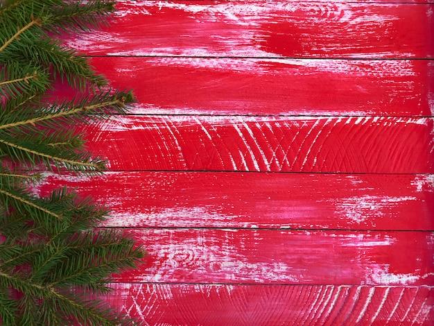 Roter hölzerner hintergrund mit fichtenzweigen rechts und einem leeren raum links