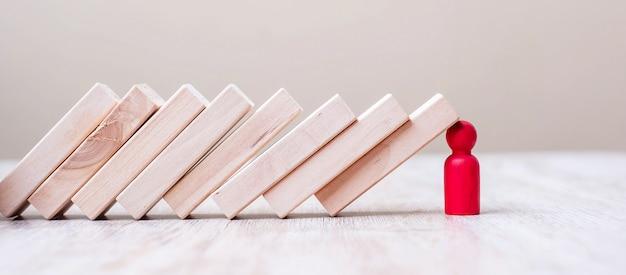 Roter hölzerner mann hört auf, blöcke auf tisch zu fallen. herbst business, planung, management, leader, versicherung, teamwork und strategiekonzepte