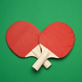 Roter hölzerner tischtennisschläger auf grünem hintergrund, paar tischtennis-sportwerkzeuge, draufsicht