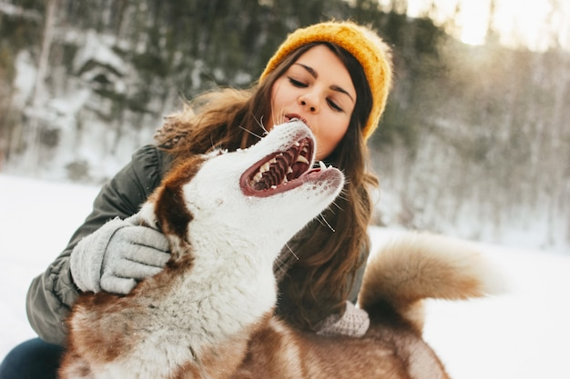 Roter hundeschlittenhund mit seinem geliebte brunettemädchen im wald draußen in der kalten jahreszeit