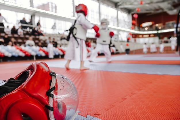 Roter kampfhelm mit durchsichtiger plastikmaske auf dem boden zwei jungen im kimono im karate-kampfkampfunschärfe