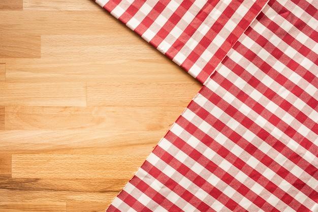 Roter karierter stoff auf holztischhintergrund. für visuelles layout der dekorationsschlüssel