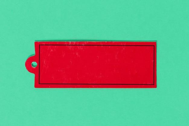 Roter kartonetikettenanhänger auf farbigem hintergrund