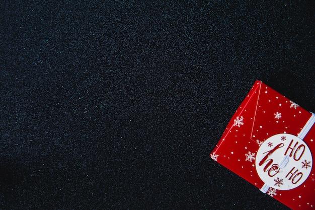 Roter kasten der weihnachtsgeschenke auf schwarzem glanz