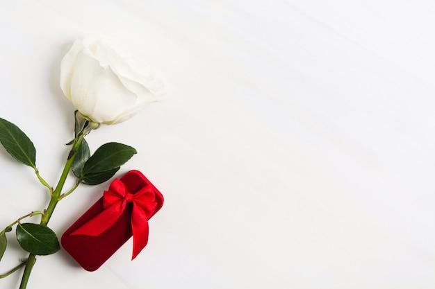 Roter kasten für schmuck mit roter bogen- und weißrose auf weißem strukturiertem hintergrund. valentinstag oder hochzeitskonzept. zeichen der liebe. kopieren sie platz