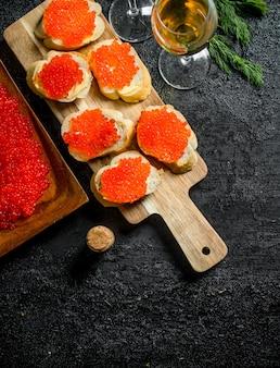 Roter kaviar auf brotscheiben und roter kaviar auf einem teller mit dem wein. auf schwarzem rustikalem hintergrund