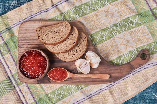 Roter kaviar auf holzbrett mit brot.