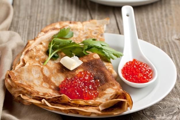 Roter kaviar auf pfannkuchen