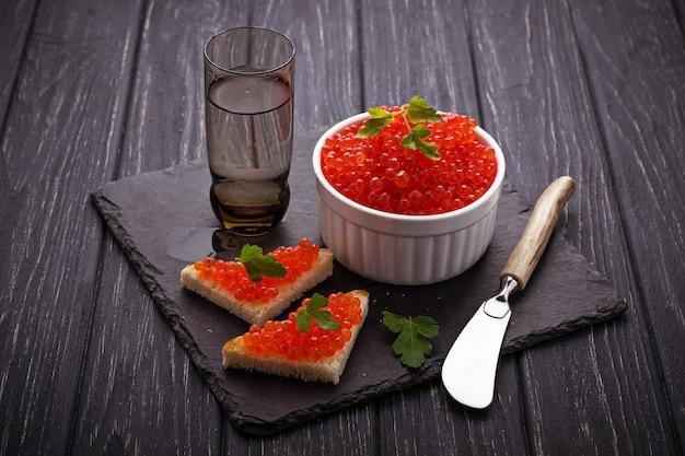 Roter kaviar auf schieferhintergrund. selektiver fokus