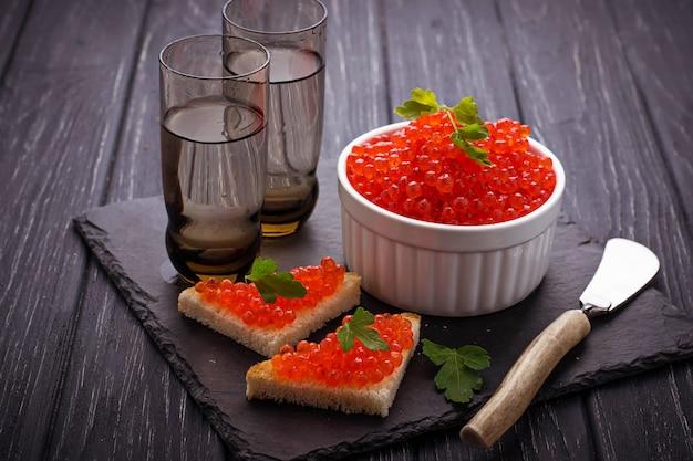 Roter kaviar auf schieferhintergrund