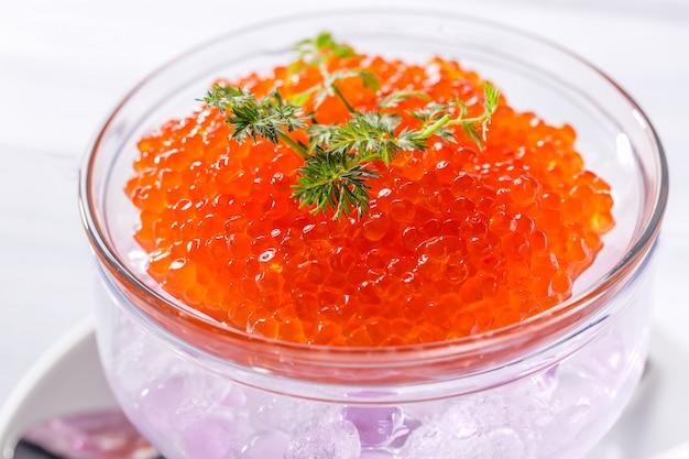 Roter kaviar im glasgefäß mit kräutern nah oben.