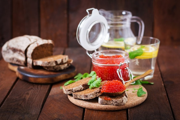 Roter kaviar in einem glas mit brotscheiben