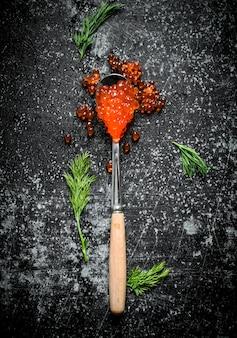 Roter kaviar in einem löffel mit dill. auf schwarzem rustikalem hintergrund