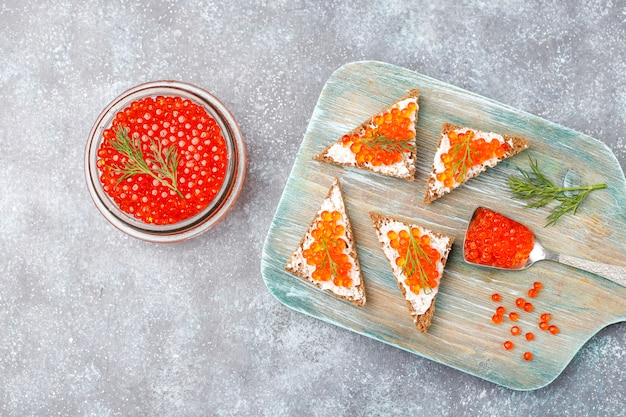 Roter kaviar in einer glasschüssel und in einem löffel