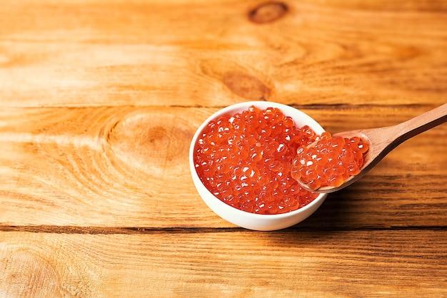 Roter kaviar in einer hölzernen tasse auf einem hölzernen hintergrund mit einem löffel.