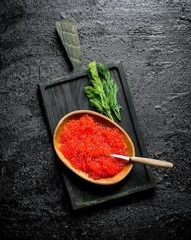 Roter kaviar in einer schüssel auf einem schneidebrett mit dill. auf schwarzem rustikalem hintergrund