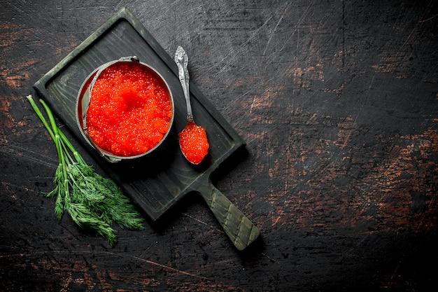 Roter kaviar in einer schüssel und ein löffel auf einem schneidebrett mit dill. auf dunklem rustikalem hintergrund