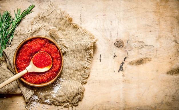 Roter kaviar in einer tasse mit rosmarin auf einem alten stoff. auf einem holztisch. freier platz für text. draufsicht