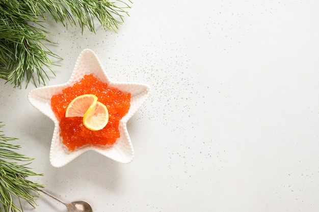 Roter kaviar in schüssel auf weißem hintergrund für weihnachtsfeier