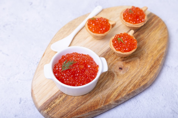 Roter kaviar (lachskaviar) in einer weißen schüssel auf einem holzbrett. im hintergrund sind törtchen mit kaviar. selektiver fokus, nahaufnahme.