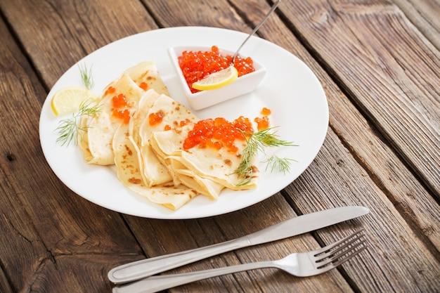 Roter kaviar mit pfannkuchen auf holztisch